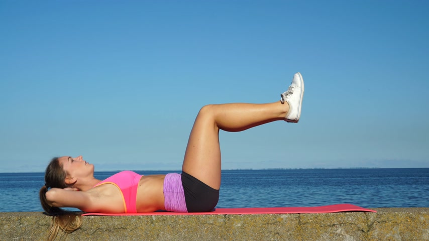 jimnastik : Woman doing sports outdoors. Fitness girl in sportswear on the seaside. 4K