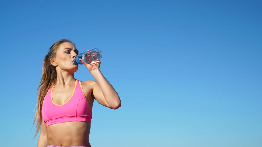 hot beverage : Woman in sportswear takes a break from the water, 4K. ProRes HQ codec.