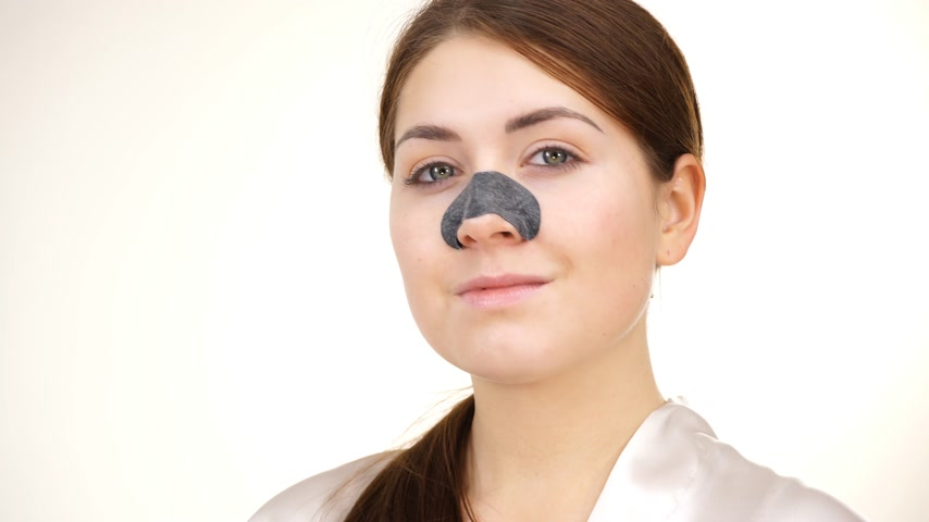 cleansing : Woman applying pore strips on nose
