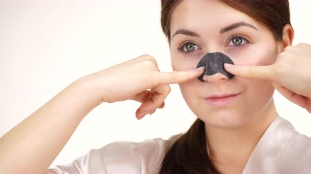 clogged : Woman applying pore strips on nose