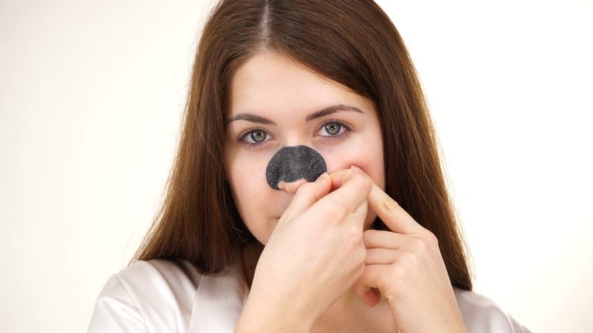 tiras : Woman removing pore strips from nose