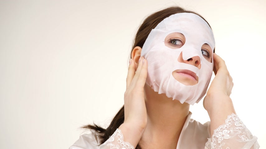 moisturize : Woman applying sheet mask on face Stock Footage