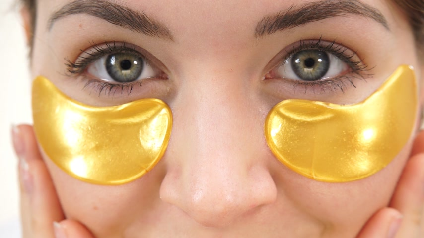 tiras : Woman gold patches under eyes closeup