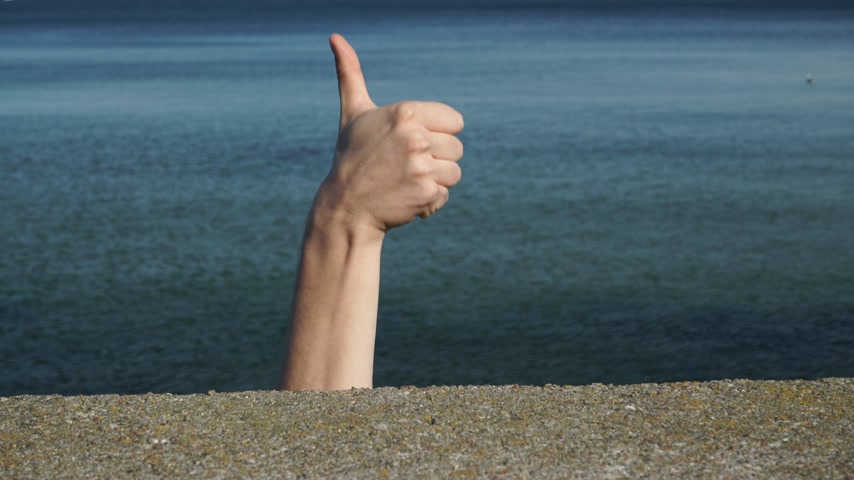 confirmed : Male hand gesturing thumb up showing cool sign against sea water. Satisfaction success symbol 4K ProRes HQ codec