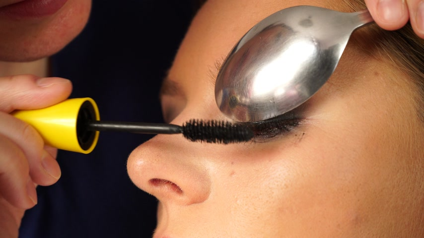 makijaż : Cosmetic beauty procedures. Closeup woman face eyes painting. Makeup artist applying black mascara is an eye model using a kitchen spoon 4K