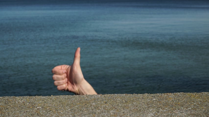 подтверждать : Male hand gesturing thumb up showing cool sign against sea water. Satisfaction success symbol 4K ProRes HQ codec