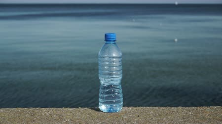 they : Water plastic bottle outdoor on sea shore. 4K with motorized slider, ProRes HQ codec