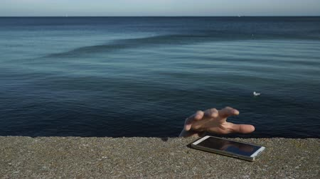 property theft : Man thief finding cell phone on the sea shore taking stealing it. Leaving belongings unattended and risk of theft. ProRes HQ codec Stock Footage
