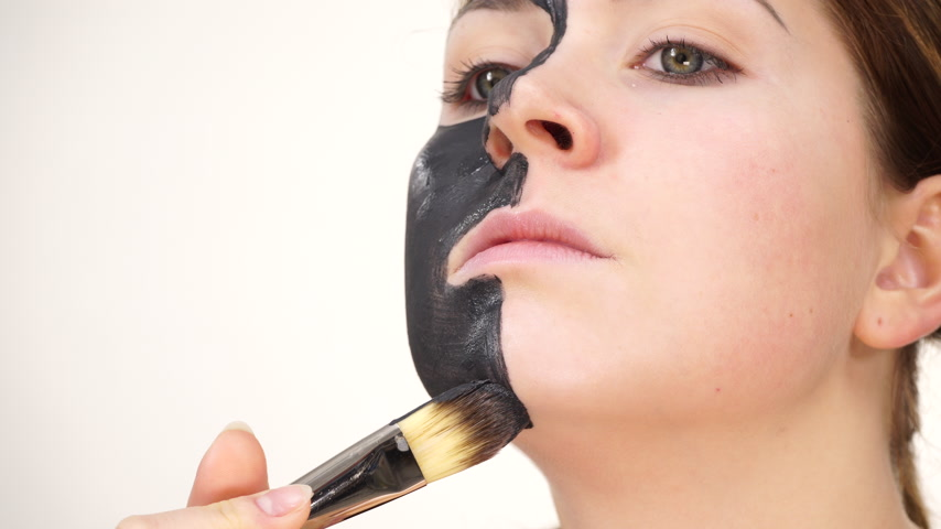 dřevěné uhlí : Woman applying black carbo mask to face