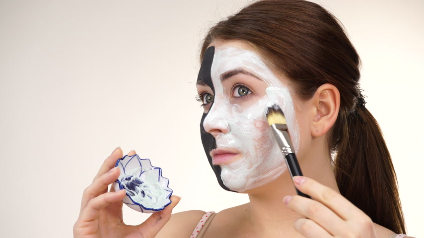 clay mask : Girl black mask on half face apply white mud Stock Footage