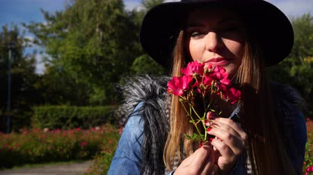 őszies : Woman holding red rose flowers in park. Fashionable girl in hat relaxing outdoor enjoying nature 4K. Prores HQ codec Stock mozgókép