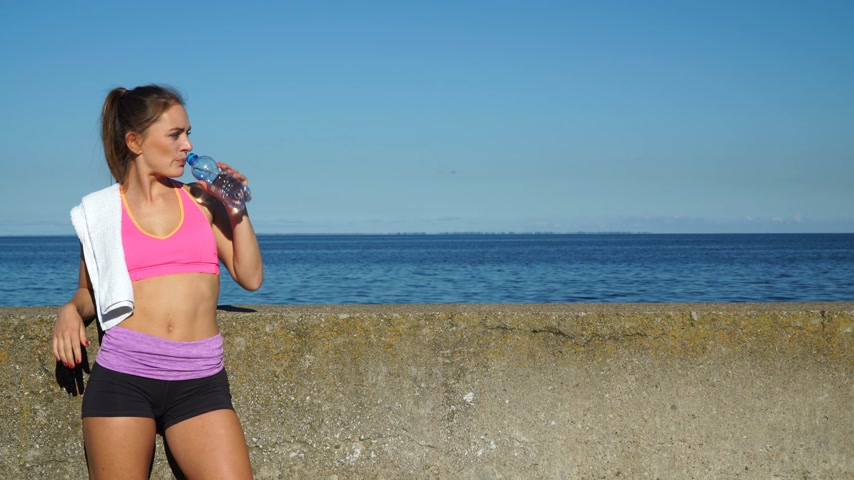 リラックスした : Woman drinking water from plastic bottle. Fitness girl in sportswear on the seaside. 4K. ProRes HQ codec 動画素材