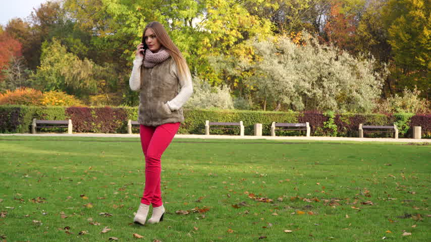 обеспокоенный : Woman talking on mobile phone smartphone in autumn fall park. Worried young girl with new technology outdoor. 4K ProRes HQ codec. Стоковые видеозаписи