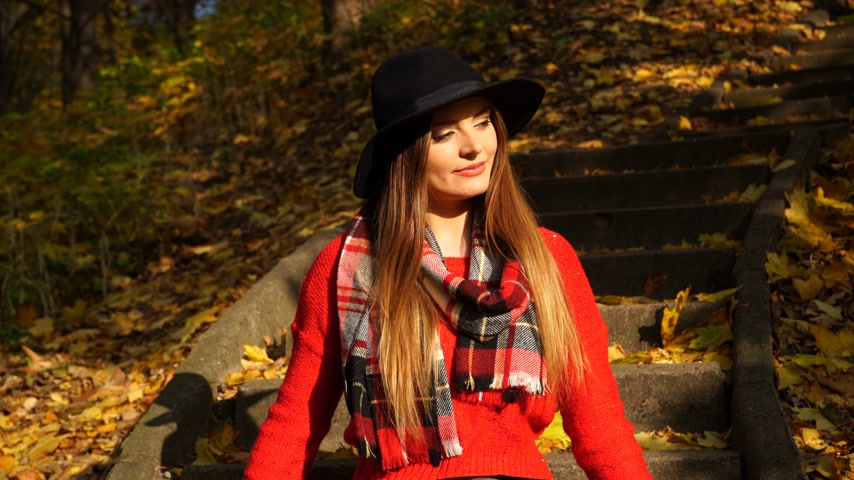 задумчивый : Woman relaxing in autumn fall park steadicam. Young pensive girl in hat sitting on stairs. 4K steadicam shot ProRes HQ codec.