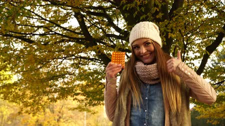 vitamine c : Woman holding pills tablets in autumn fall park forest. Young girl in jacket and scarf giving thumb up gesture. Health care. 4K ProRes HQ codec.