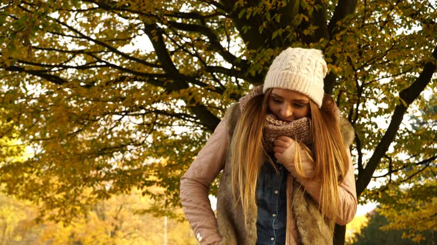 c vitamini : Woman with pills tablets shivering in autumn fall park forest. Young girl in jacket and scarf outdoor. Health care. 4K ProRes HQ codec. Stok Video