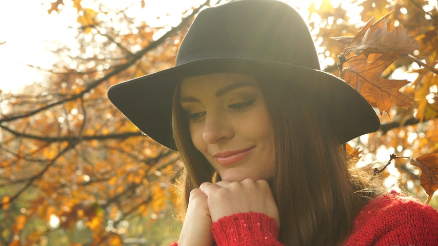 задумчивый : Woman relaxing in autumn park forest. Young pensive girl in hat thinking dreaming outdoor. 4K ProRes HQ codec. Стоковые видеозаписи