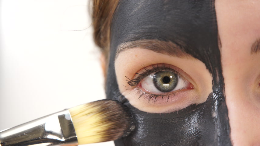 лицевой : Woman applying black carbo mask to face