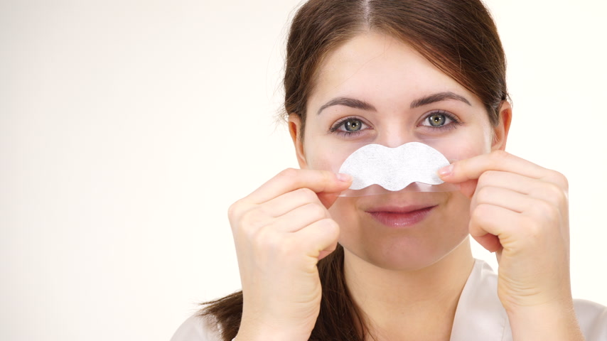 folt : Woman applying pore strips on nose