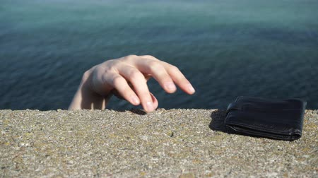portemonee : Man thief finding wallet on the sea shore. Leaving belongings unattended and risk of theft. ProRes HQ codec
