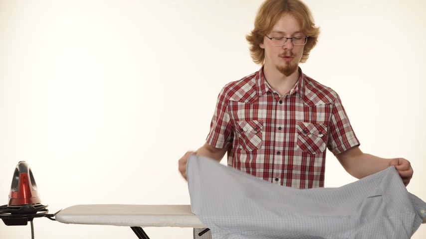 гладильный : Hipster man irons clothes on ironing board 4K Стоковые видеозаписи