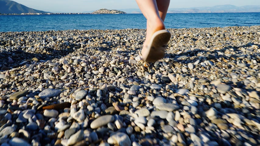 peloponnese : Woman walking to water on beach, back view Stock Footage