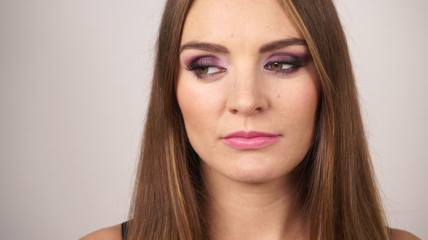 внимательный : Woman face alluring female long hair girl with dark makeup violet color shadows on eyelids. Pensive sad facial expression 4K ProRes HQ codec Стоковые видеозаписи