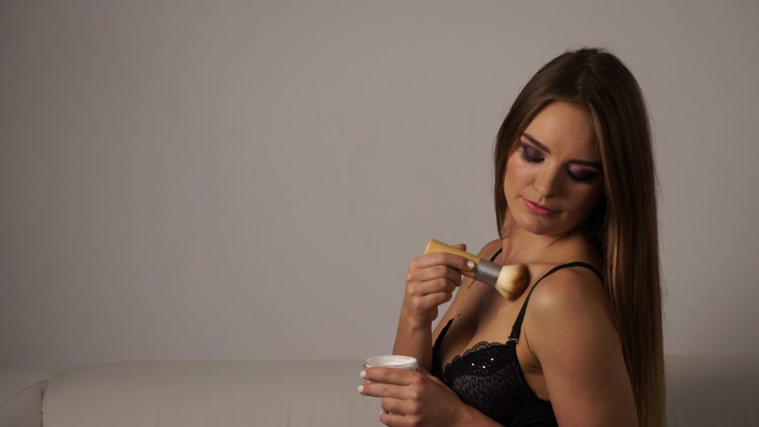 seio : Woman in black lingerie applying anti-shine powder with brush to her body neckline. Pretty gorgeous girl beautifying. Fashion and makeup. 4K ProRes HQ codec