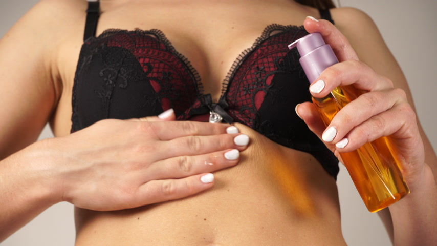 pleťová voda : Woman applying moisturizing body oil lotion on belly. Female girl in underwear with moisturizer bottle. Skincare. 4K ProRes HQ codec.