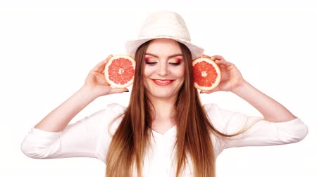 grejpfrut : Woman attractive long hair girl colorful eyes makeup holding two halfs of grapefruit citrus fruit in hands. Healthy diet food. Summer vacation holidays concept 4K ProRes HQ codec