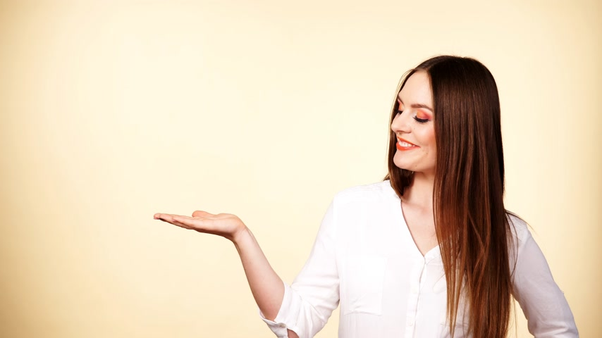 indicating : Woman showing presenting, long-haired girl holding empty copy space for product. Beauty, fashion, advertisement concept. Studio shot on bright background 4K ProRes HQ codec Stock Footage
