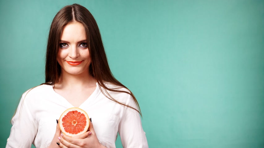 grejpfrut : Woman with long hair holding grapefruit citrus fruit in hand. Healthy diet food. Summer vacation holidays concept. Studio shot on green 4K ProRes HQ codec