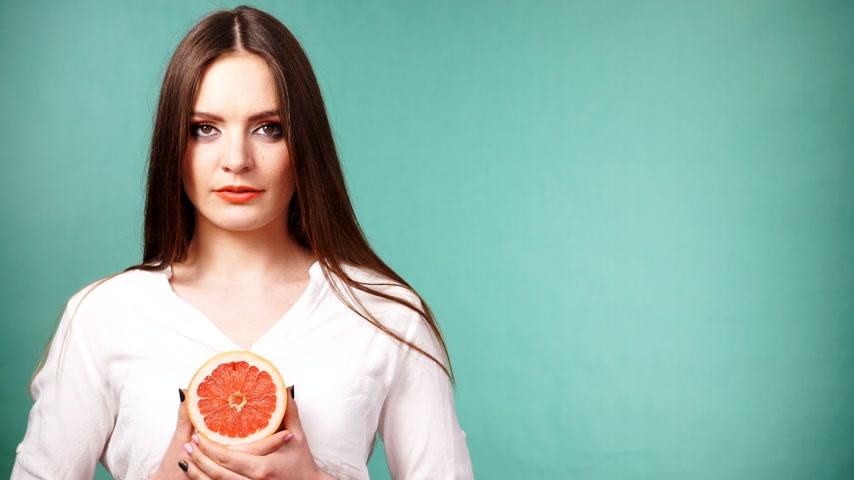 pompelmoes : Woman with long hair holding grapefruit citrus fruit in hand. Healthy diet food. Summer vacation holidays concept. Studio shot on green 4K ProRes HQ codec