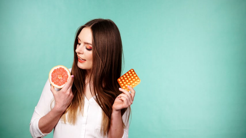sentetik : Woman holding pills blister pack vitamin c in hand and grapefruit in another. Choice between natural and synthetic way of health care. Alternative medicine. Studio shot on green background 4K ProRes HQ codec Stok Video