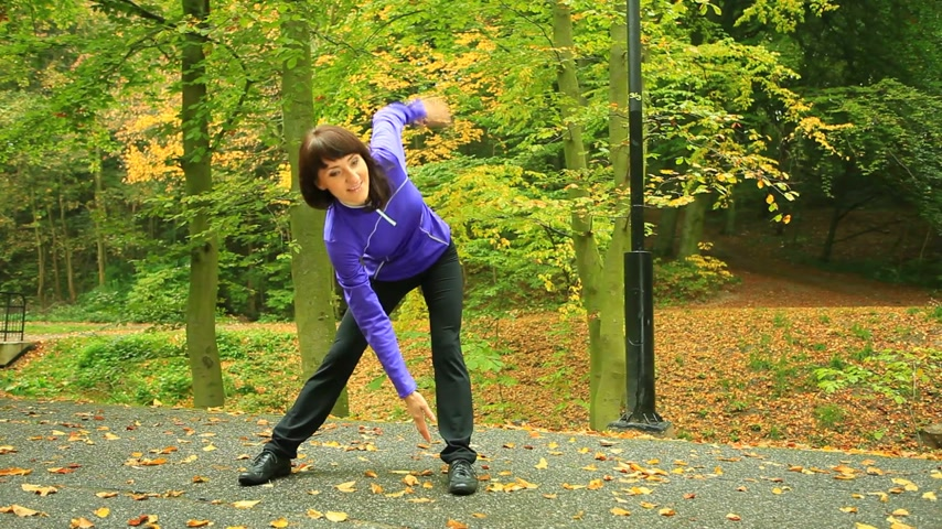 squats : Healthy active lifestyle health care. Fitness woman doing exercise squats outdoor, training workout. Girl fit fitness sport female stretching outside in autumn fall park. Forward sliding shot. Full HD, dolly shot.