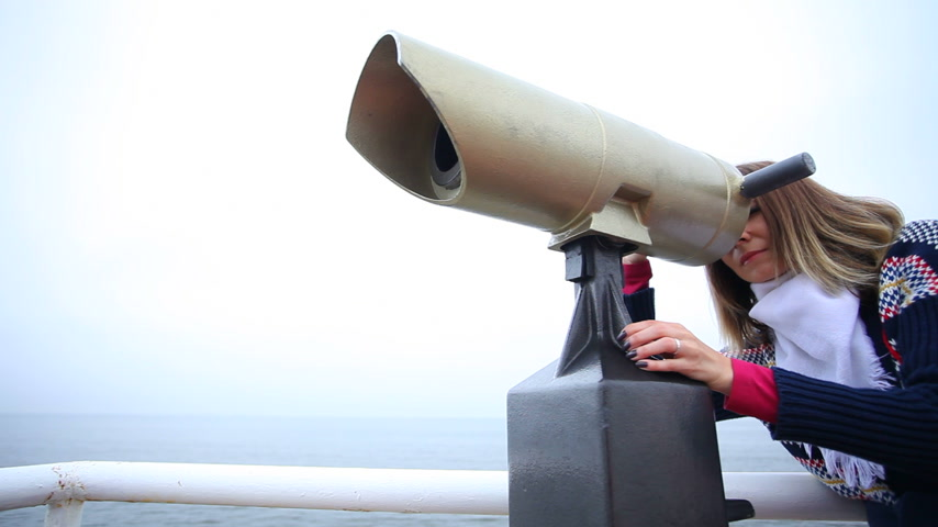 distante : Travel and tourism. Woman looking through binoculars at the sea or ocean shore. Resort. Full HD with motorized slider. 1080p.