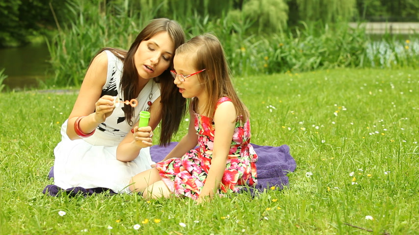 sopro : Summer. Mother with little daughter having fun. Young woman and girl child blowing soap bubbles outdoor. Stock Footage