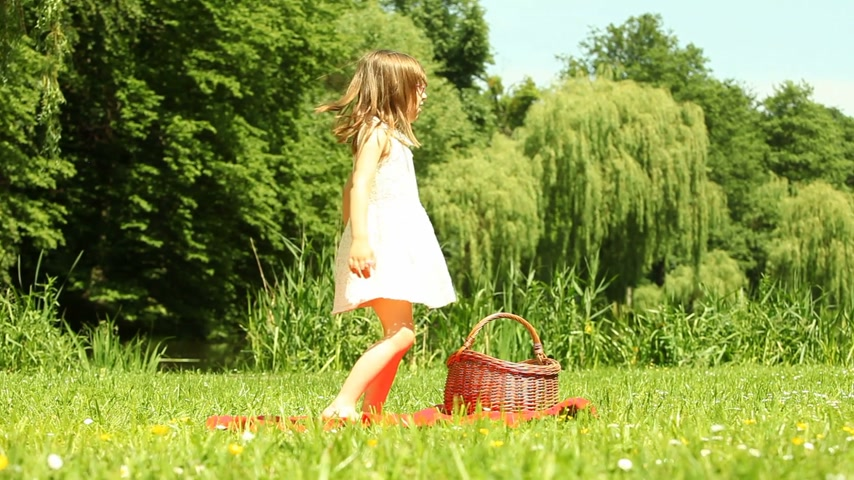 whirling : Summer. Little girl dancing on the meadow. Cute child having fun in the park.