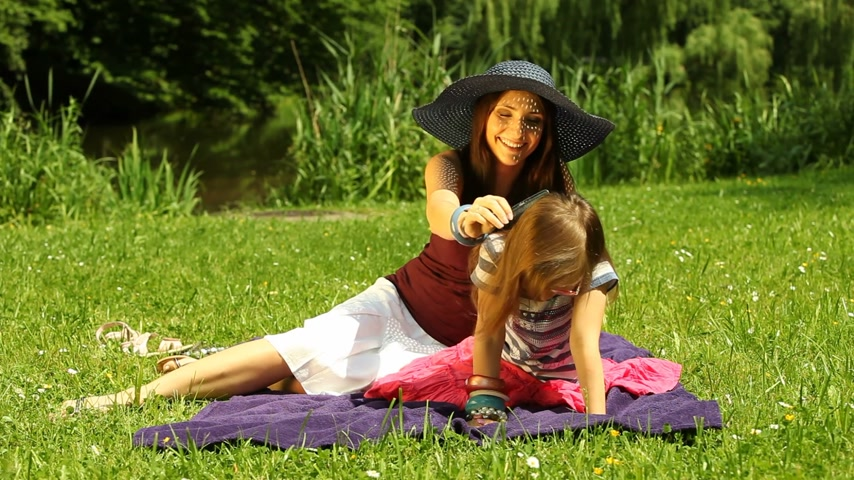 tongue out : Summer. Mother and daughter in a straw hat. Girl child kid sticking out her tongue at camera. Stock Footage
