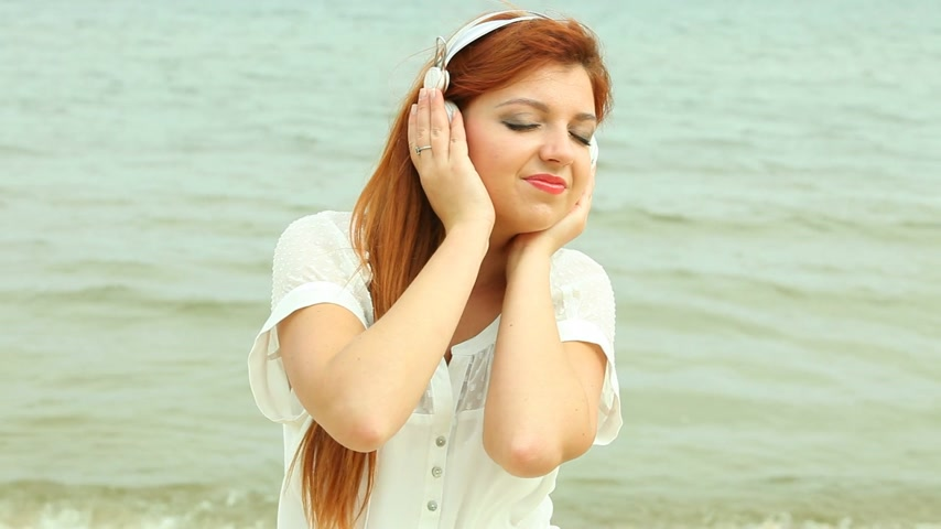 saçlı : Woman with headphones Listening to Music on Beach