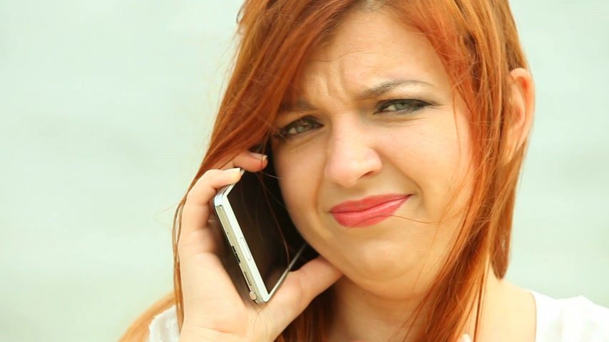 they : Red haired woman using smartphone on beach