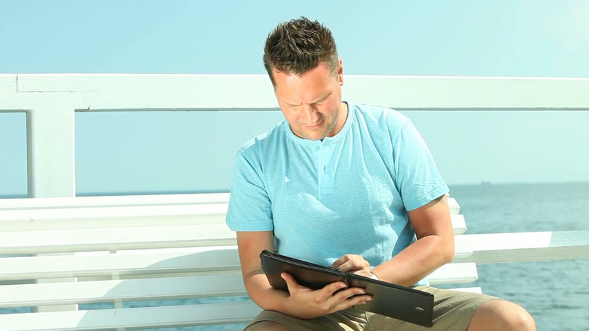 they : Man using tablet by sea Stock Footage