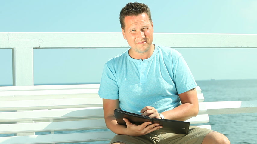 Man using digital tablet by sea