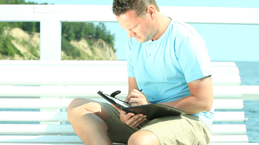 Man using tablet by sea Wideo