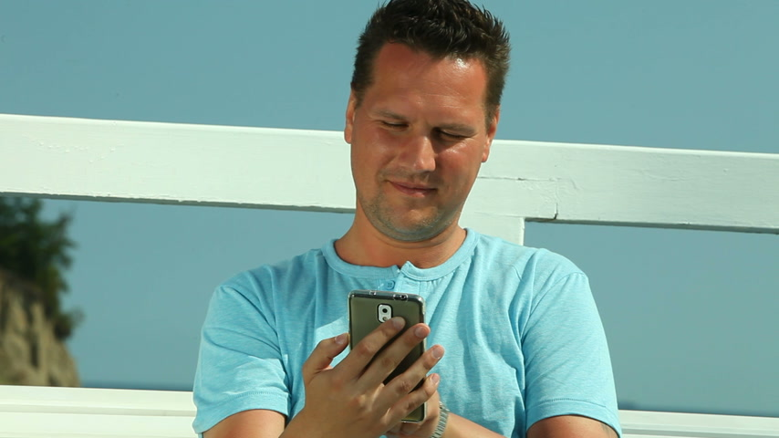 they : Happy man with smartphone by sea Stock Footage