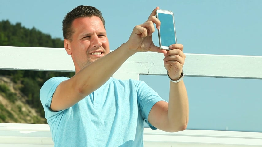 Man taking photo with smartphone by sea Стоковые видеозаписи