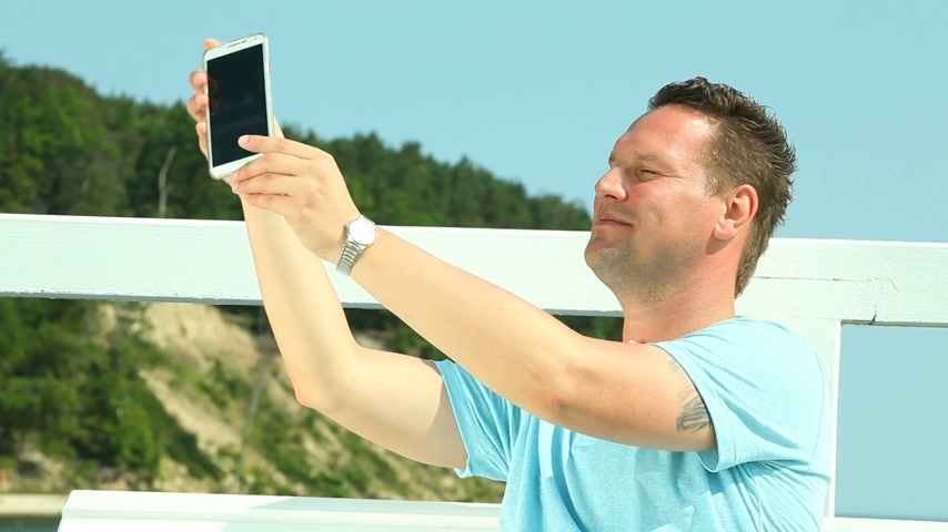 Man taking photo with smartphone by sea Wideo