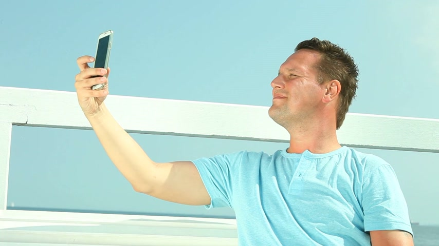 Man taking photo, selfie with smartphone at pier