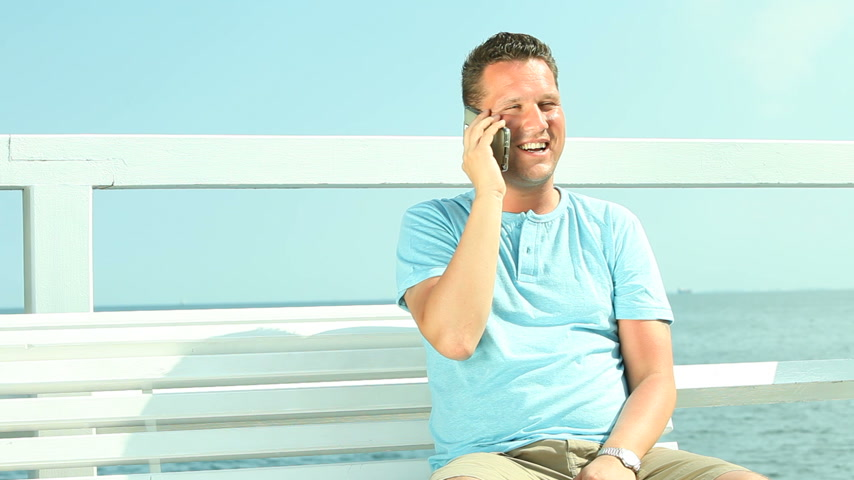 Happy man with smartphone sitting on bench by sea