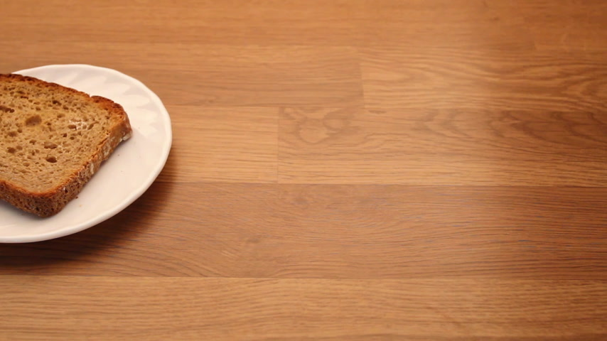パン粉 : Food. Slice of rye brown bread on plate, kitchen wooden table background. Full HD with motorized slider. 1080p 動画素材